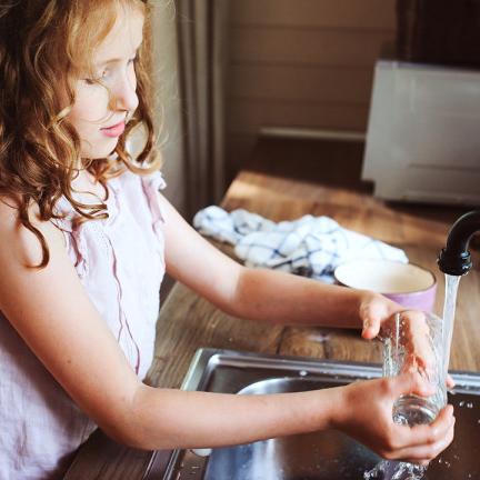 Child washing dishes doing chores
